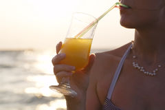 Woman sipping a refreshing cocktail at sunset Stock Image