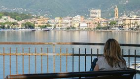 Woman sit bench city sea bay skyline back view Rapallo Italian Riviera Italy stock video