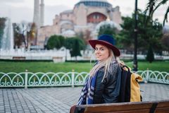 Woman traveling in Istanbul near Aya Sofia mosque, Turkey. Woman sit on the bench and enjoy beautiful view on Aya Sofia mosque, Travel to Istanbul, Turkey royalty free stock photography