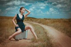 Woman sit on a case nature portrait Stock Image