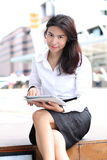 Woman sit in foreground with a tablet in her hands moder buildin Stock Images