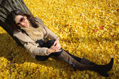 Woman sit on ground be filled with leaves of ginkgo tree in fall Stock Photos