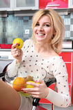 Woman sit in the kitchen with fruit Stock Photography