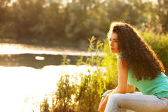 Woman sit by lake. Young curly hair woman enjoy in summer sun at lake Stock Image