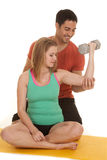 Woman sit man behind help fles weights Royalty Free Stock Image