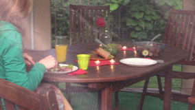 Woman sit near table with burn candle and eat. Romantic supper stock video