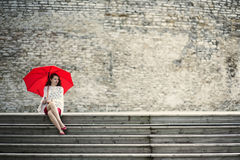 Woman sit with open umbrella at steps Stock Images