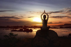 Woman sit over the rock doing yoga Stock Photo