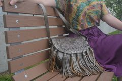 Woman sitting in a bench with violet skirt. A woman sit in a park bench. She is wearing a violet skirt and a multicolor shirt. she has a silver leather bag Stock Image