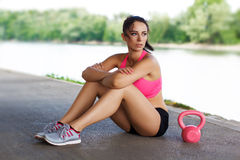 Woman sit with pink kettlebell Stock Photos