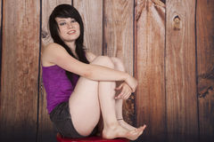 Woman sit red chair wood background legs up Royalty Free Stock Photography