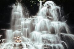 Woman sit on rock in yoga pose under cascade waterfall Royalty Free Stock Image