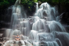 Woman sit on rock in yoga pose under cascade waterfall Stock Image