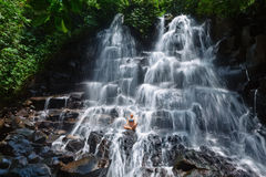 Woman sit on rock in yoga pose under cascade waterfall Stock Photography