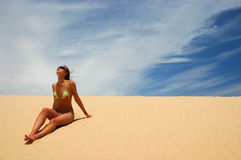Woman sit on the sand. Woman in sunglasses sit on the sand and look up Stock Image