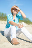 Woman sit sea shore Stock Images