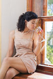 Woman sit on sill and smells wine Stock Photo