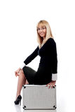 Woman sit on a silver case Stock Images