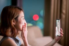 Woman chating online with friend. Woman sit on sofa and chating online with friend at night royalty free stock photography
