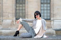 Woman sit on stone fence on house facade. Girl with brunette hair, red lips in sunglasses. Model in high heel shoes, fashionable clothes. Fashion, vogue Royalty Free Stock Photo