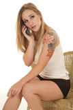 Woman sit tattoo phone serious Stock Photos