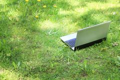 Woman sit to use silver laptop at parks in the city with gold light.  Stock Photography