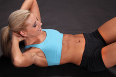 Woman Sit-ups. An attractive young female woman in black shorts and blue top training or working out by doing sit-ups isolated against a black background Stock Photography