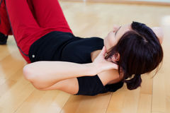 Woman sit ups. Healthy female lying on the floor and doing sit ups Royalty Free Stock Images