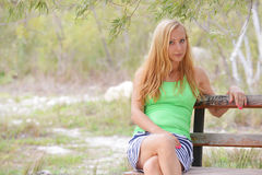 Woman sit on wooden bench Stock Photos