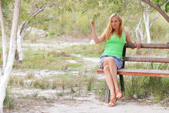 Woman sit on wooden bench Stock Photography