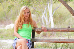 Woman sit on wooden bench Stock Photo