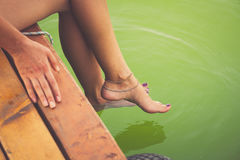 Woman sit on wooden dock cooling feet in clear water. Young woman sit on wooden dock by river or lake cooling feet in clear water hot summer day Royalty Free Stock Photography