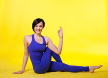 Woman sit in yoga pose - padmasana on yellow Stock Photos