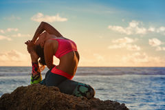 Woman sit in yoga pose on sunset sea beach. Meditation on sunset sky background. Young active woman sit in yoga pose on beach rock, stretching to keep fit and Stock Image