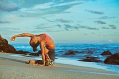 Woman sit in yoga pose on sunset sea beach. Meditation on sunset sky background. Young active woman sit in yoga pose on sand beach, stretching to keep fit and Royalty Free Stock Photo