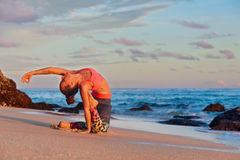 Woman sit in yoga pose on sunset sea beach. Meditation on sunset sky background. Young active woman sit in yoga pose on sand beach, stretching to keep fit and Royalty Free Stock Image