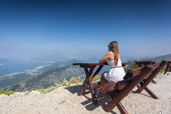 Woman siting on bench on top of mountain and looking at landscap Royalty Free Stock Photos