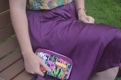 Woman sitting in a bench with violet skirt. A woman siting in a bench. She is wearing a violet skirt and a  shirt. she has a violet  bag. Retro bicycle Royalty Free Stock Photography
