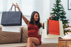 Woman siting by the christmas tree and taking a present out of shopping bag stock image