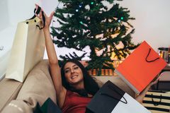 Woman siting by the christmas tree and taking a present out of shopping bag stock images