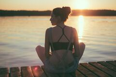 Woman Siting on Dock Near Large Body of Water Royalty Free Stock Photography