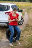 Young woman siting next to broken car and searching for auto service number in mobile phone. Woman siting next to broken car and searching for auto service royalty free stock photo