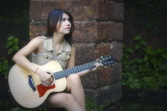 Woman siting and playing guitar stock images