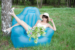 Woman sits in an arm-chair Royalty Free Stock Photos