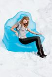 Woman sits in an arm-chair outside in winter Royalty Free Stock Image