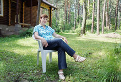 Woman sits in an armchair on the glade in a forest Royalty Free Stock Images