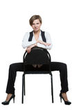 Woman sits astride a chair. arms crossed. dominant Royalty Free Stock Photography