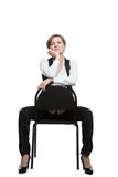 Woman sits astride a chair. hand under chin. Misses. dominant position. Isolated on white background Royalty Free Stock Photos