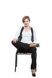 Woman sits astride a chair. legs crossed, fixed. Arm. misses. dominant position. Isolated on white background Stock Image