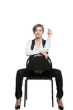 Woman sits astride a chair. sexy shows wrist. Dominant position. Isolated on white background Stock Image